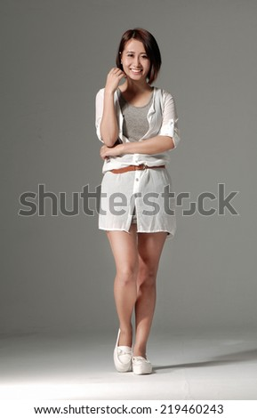 Full body portrait of happy smiling beautiful young woman, isolated over gray background - stock photo