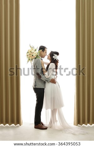 full body portrait of romantic asian newlywed couple embracing each other on white background with curtain - stock photo