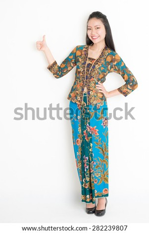 Full body portrait of Southeast Asian woman in batik dress giving thumb up, standing on plain background. - stock photo