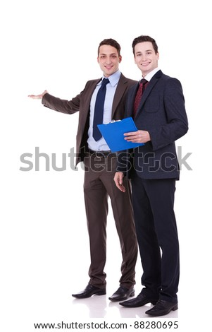 full body portrait of two young business men presenting something at their back - stock photo