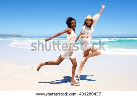 Full body portrait of two young women friends laughing and running on the beach - stock photo