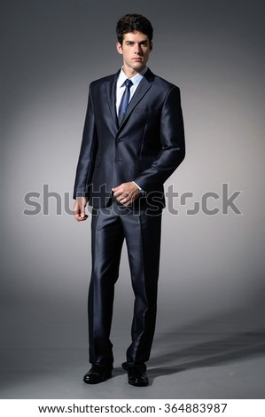 Full body Portrait of young business man in studio - stock photo