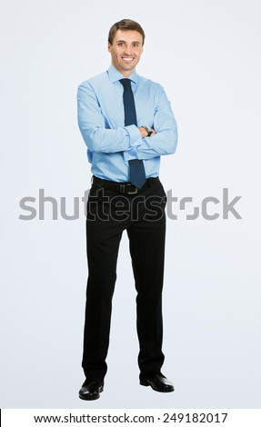 Full body portrait of young happy smiling business man, over grey background - stock photo