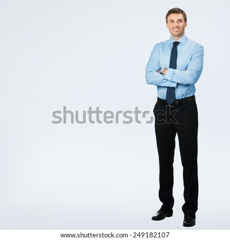 Full body portrait of young happy smiling business man, over grey background, with copyspace area for text or slogan - stock photo
