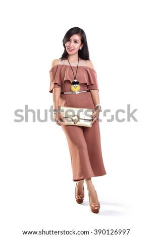 Full body shot of attractive adult Asian woman in stylish fashion posing with her purse, isolated on white background - stock photo