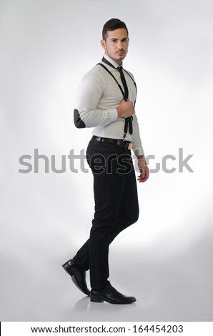 Full body shot of elegant and stylish young man on light background, profile standing - stock photo