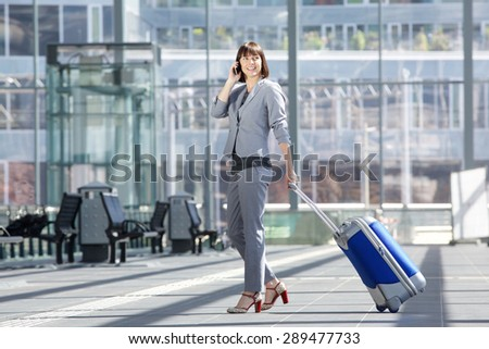 Full body side portrait of a smiling business woman walking with bag and mobile phone - stock photo