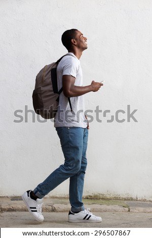 Full body side portrait of a smiling male college student walking with bag and mobile phone - stock photo