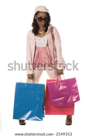 Full body view of a Beautiful young African American girl wearing super model sunglasses and a little hat and shopping it up like a true Hollywood Diva carrying an assortment of colorful shopping bags - stock photo