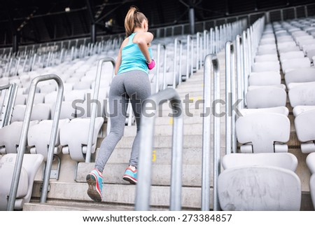 Full body workout at stadium, healthy female doing fitness exercises. Female running on stairs - stock photo