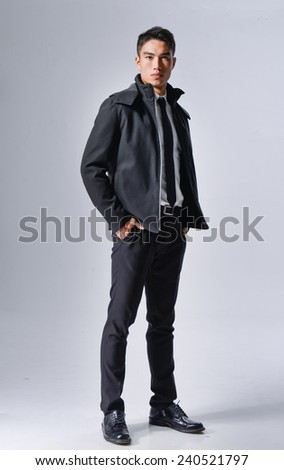 Full body young businessman standing with his hands in the pockets. - stock photo