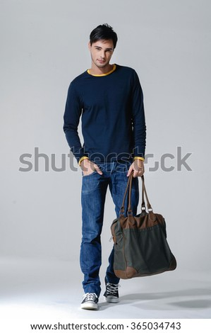 Full body young Casual man walking holding a bag over isolated - stock photo