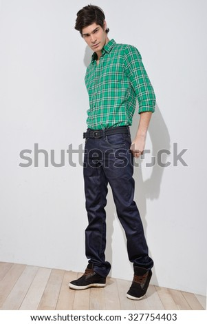 Full body Young handsome male in jeans posing in full length over wooden background - stock photo
