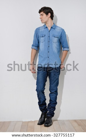 Full body young man in casual clothes posing over wooden background. - stock photo