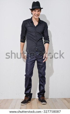 Full body young Man in Casual Clothes with hat in wooden floor - stock photo