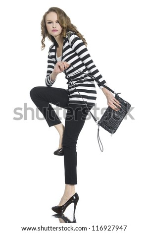 Full body young woman in stripy shirt and jeans with bag posing - stock photo