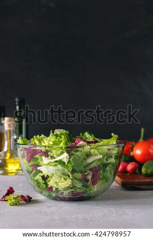 Full bowl of fresh green salad on a light table against a dark background on a rustic kitchen. Concept helpful and simple food - stock photo