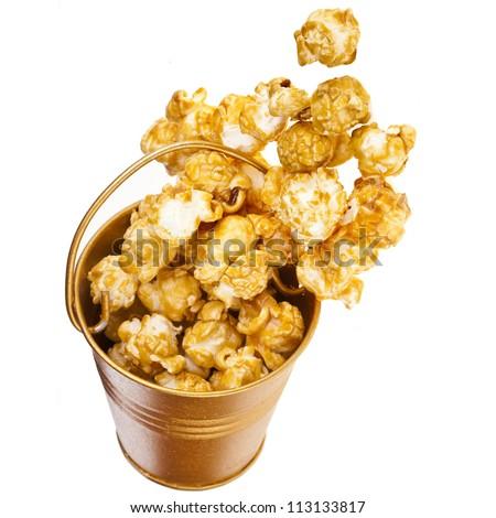 Full bucket box of caramel popcorn dropped isolated on white - stock photo