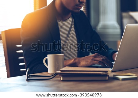 Full concentration. Close-up part of young African man using laptop while sitting at his working place - stock photo