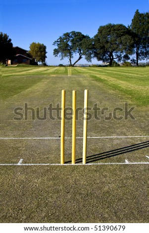 Full Cricket pitch with wickets and creases in the morning before play commences - stock photo