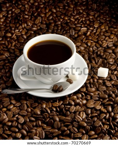full cup of coffee on beans - stock photo