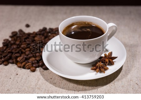 Full cup of dark coffee in white teacup and saucer beside spices and beans in the background on tablecloth - stock photo