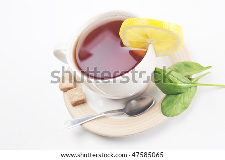 full cup of tea with lemon and sugar - stock photo