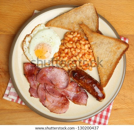 Full English breakfast with bacon, sausage, fried egg, baked beans and fried bread. - stock photo