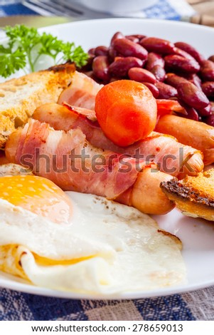 Full English breakfast with bacon, sausage, fried egg, baked beans and tea. - stock photo