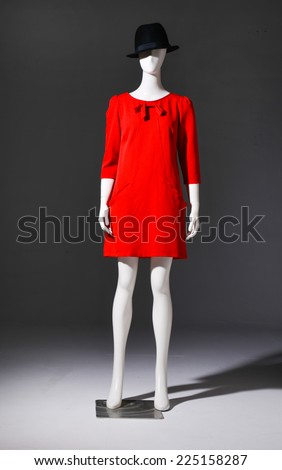 Full female red clothing with black cap on mannequin on gray background - stock photo