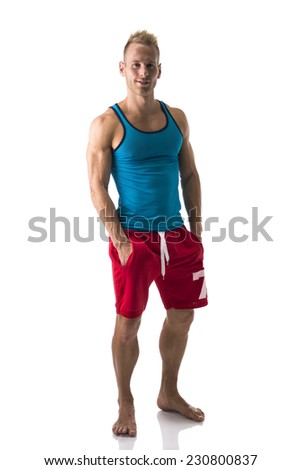 Full figure of muscular, young man standing confident barefoot, smiling at camera isolated on white - stock photo