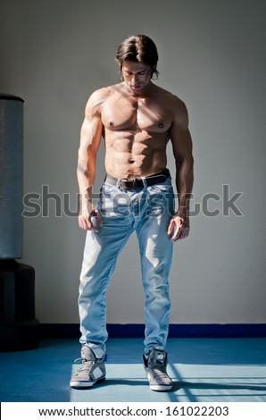 Full figure shot of muscular man shirtless in jeans, looking down - stock photo