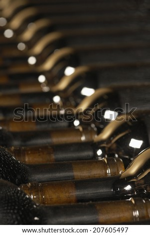 Full frame shot of arranged wine bottles in the cellar - stock photo