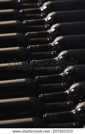 Full frame shot of bottles arranged in wine cellar - stock photo
