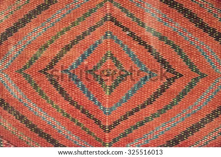 Full frame shot of Mexican native art pattern on a cloth. The art has zig-zag lines forming squares with in squares on an orange background. The Textiles of Mexico have a long history.  - stock photo