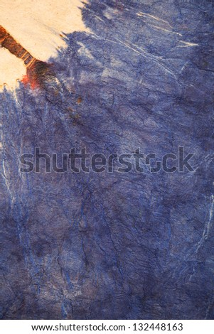 Full frame view of a hand made old piece of textured paper with navy blue batik dye. - stock photo