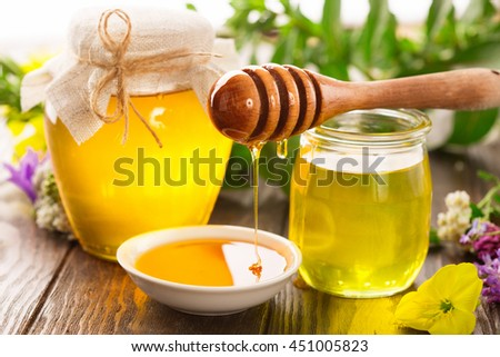 Full fresh honey pot and honey stick with summer flowers on rustic wooden table, selective focus - stock photo
