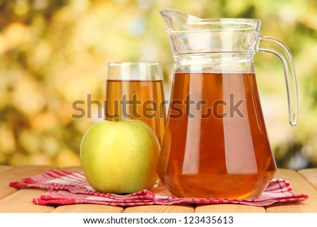 Full glass and jug of apple juice and apple on wooden table outdoor - stock photo