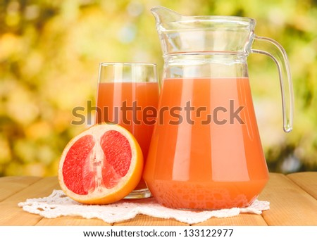 Full glass and jug of grapefruit juice and grapefruits on wooden table outdoor - stock photo