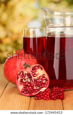 Full glass and jug of pomegranate juice and pomegranate on wooden table outdoor - stock photo