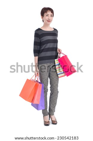 Full happy beautiful woman with shopping bags posing in studio - stock photo