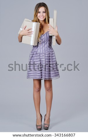 Full height portrait of a beautiful happy woman in gala dress holding present boxes - stock photo