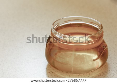 full honey pot glass, jar of organic floral honey or syrup on table - stock photo