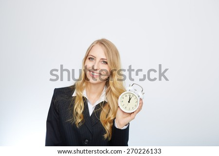 Full isolated portrait of a beautiful caucasian businesswoman locking at the clock with pointer 5 to 12. - stock photo