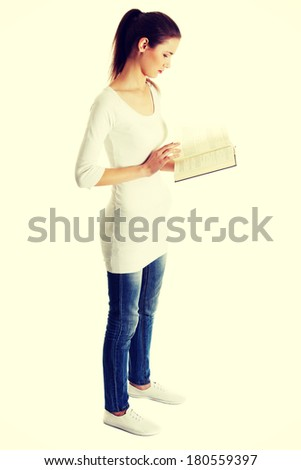 Full lenght portrait of a beautiful young caucasian teen reading a Bible, on white. - stock photo