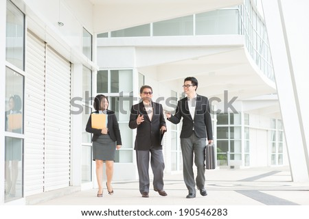 Full length Asian business team meeting, walking and having discussion over office. - stock photo