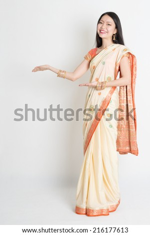 Full length Asian Indian girl hands showing something on plain background. - stock photo
