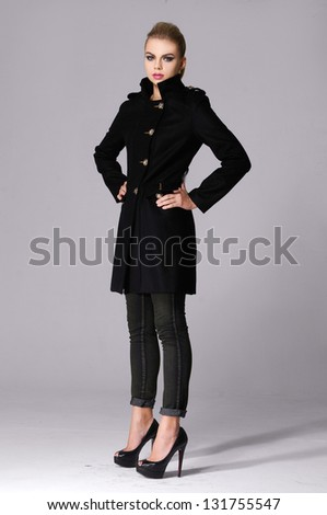full length attractive young girl in a black coat standing against gray background - stock photo