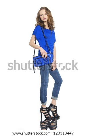 Full length beautiful fashion woman in jeans with blue bag posing - stock photo