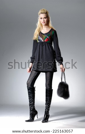 full-length Beautiful Young Model holding bag posing in light background - stock photo